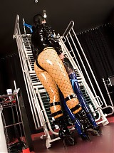 Slave girl is bound to the iron frame