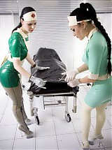Two rubber nurses checkup patient dressed up in black rubber outfit with big boobs
